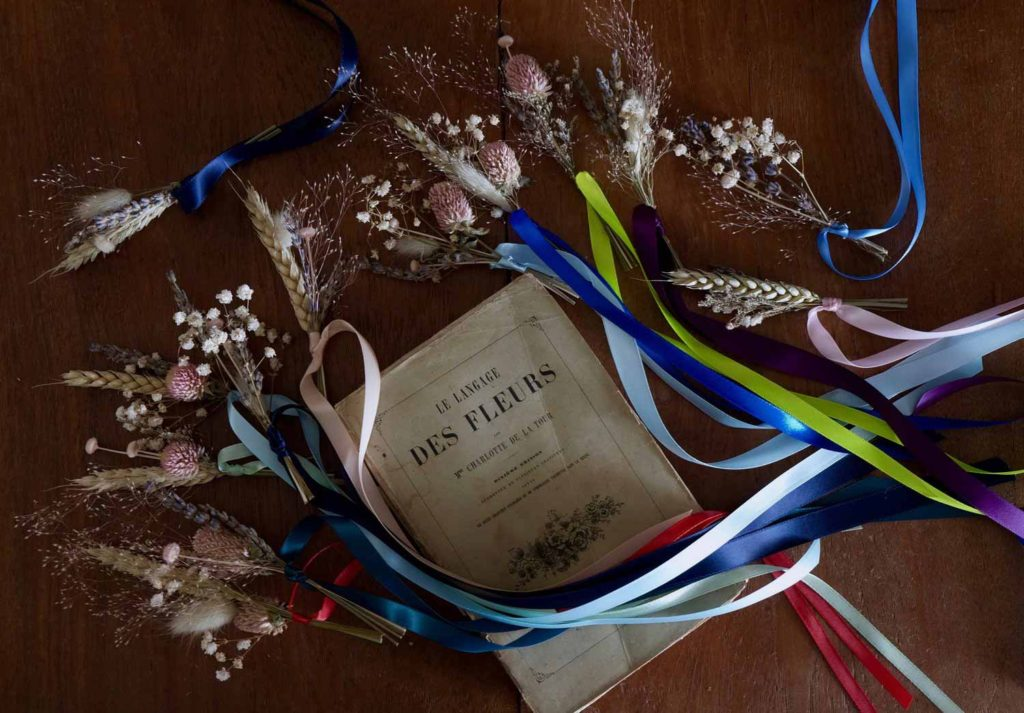 little composition of a french book of poems with dried flowers around it and some ribbons