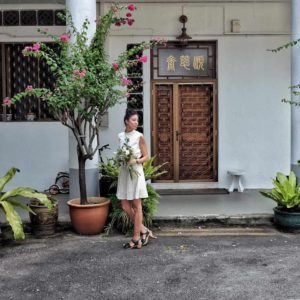 Aude Giraud outside in Singapore at Tiong Bahru holding flower and wearing a all white outfit