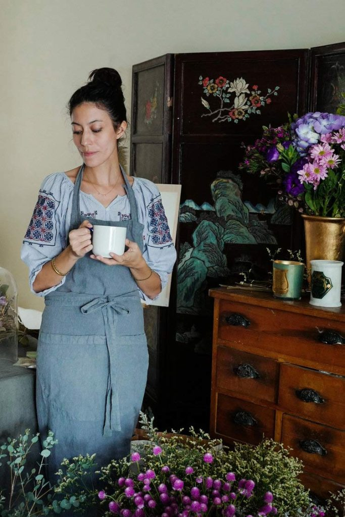 Aude Giraud amoung her flowers with a cup of hot tea in hr hands