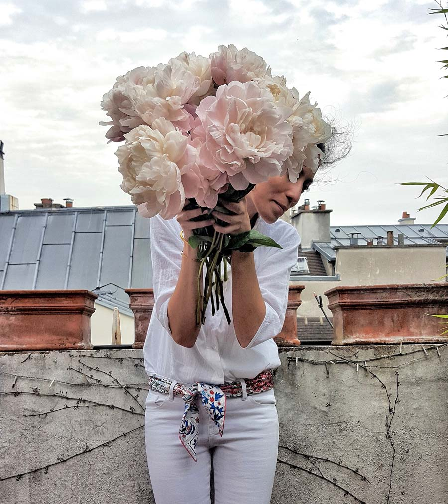 woman holding a huge bouquet of pink flowers