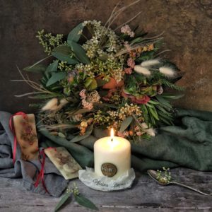 a christmas wreath flower bouquet with a burning white candle