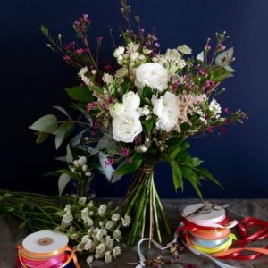 big flower bouquet with white roses and purple flowers set up with colorful rubans