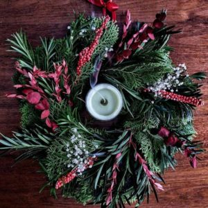 a christmas wreath centered on a table with a burning scented candle in the middle